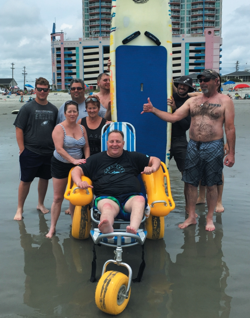 Tracy Price poses with relatives and volunteers with Wheel to Surf after they took him surfing in Cherry Grove in May—the first time Price had been in the ocean since he became dependent on a wheelchair after an ATV accident in 2004.